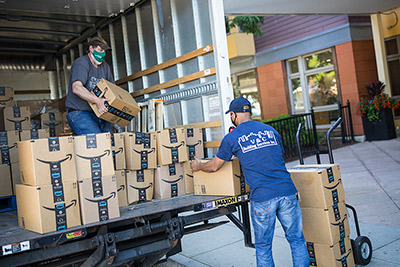 Delivery men unloading boxes of food