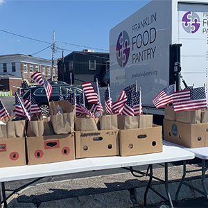 Franklin Food Pantry's Summer Fun Bags outside for distribution with American flags